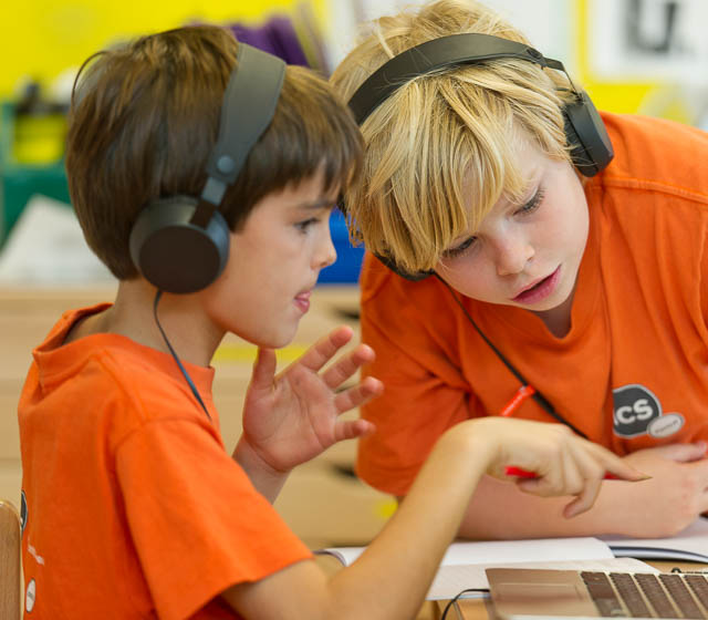 primary school students with headphones working together, international school