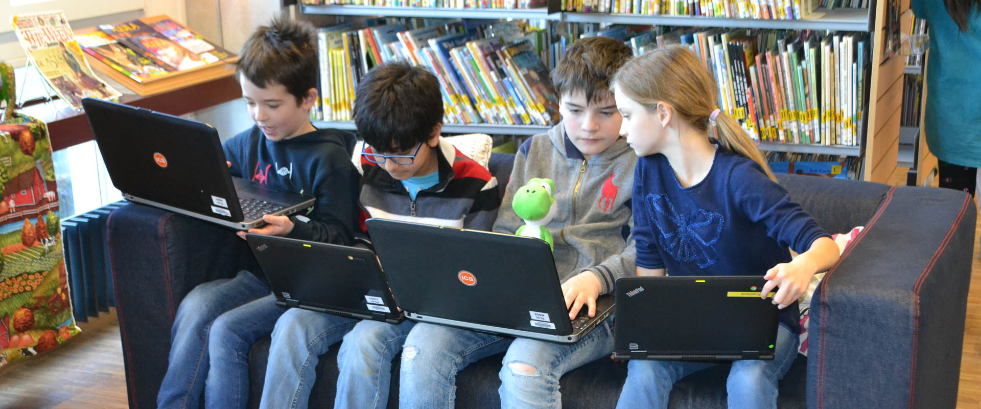 students learning with their laptops at the library and media centre as part of the digital citizenship programme, international school