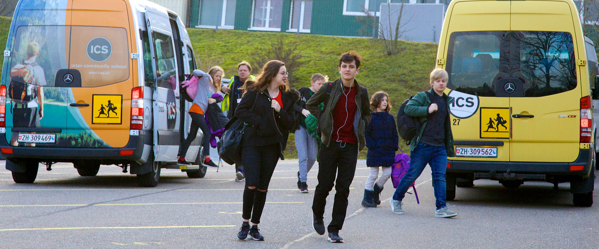 students arriving to school by school bus, international school