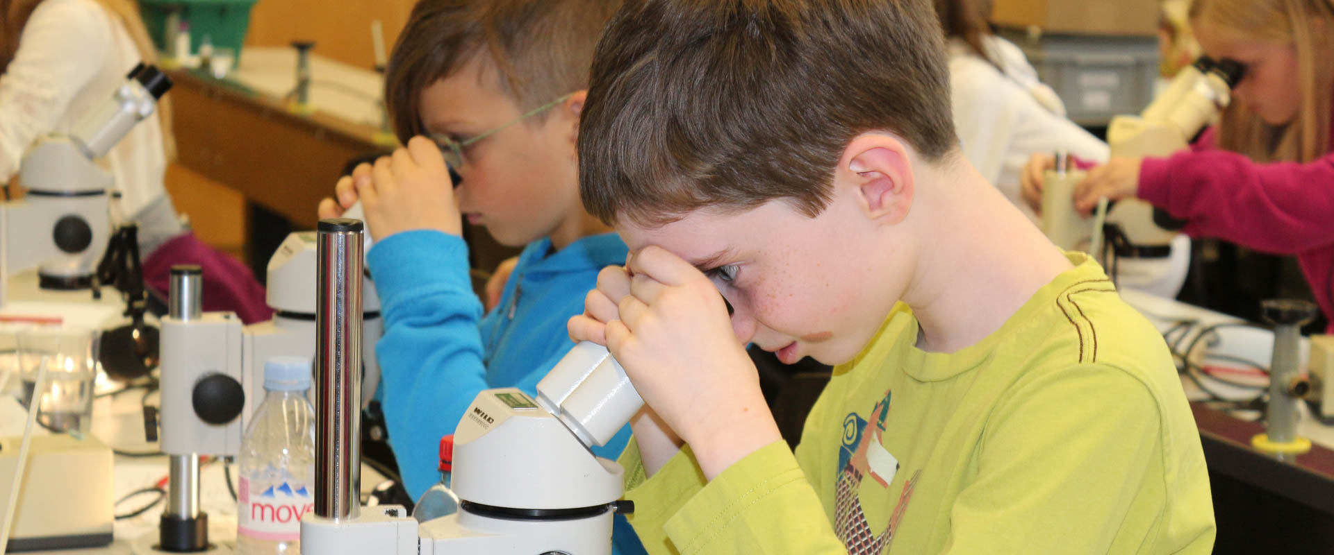 primary school students looking through microscopes on a visit to the ETH laboratory, international school
