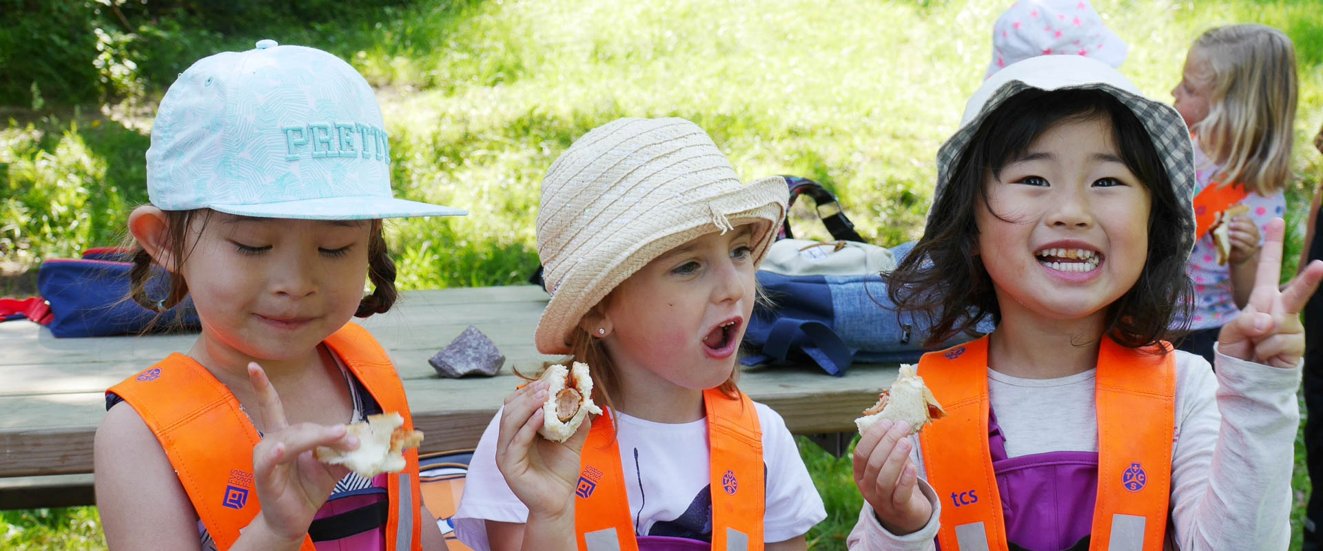 primary school students eating together outdoors, international school