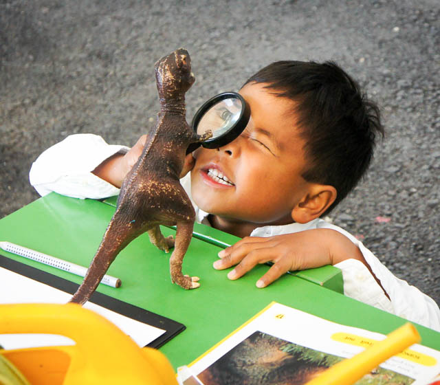 bilingual preschool student looking through a magnifying glass at a toy dinosaur, preschool/kindergarten/early years programme, international school
